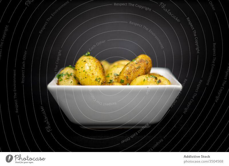 Bowl of baked potatoes with herbs roast bowl table cafe timber food meal dinner dish lunch fresh ingredient lumber black palatable gourmet cuisine delectable