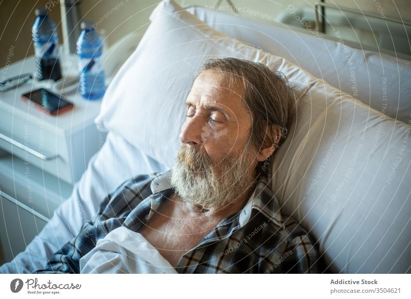 Senior man sleeping in hospital bed senior ward elderly patient medicine illness tired clinic old blanket recovery disease control age unwell problem
