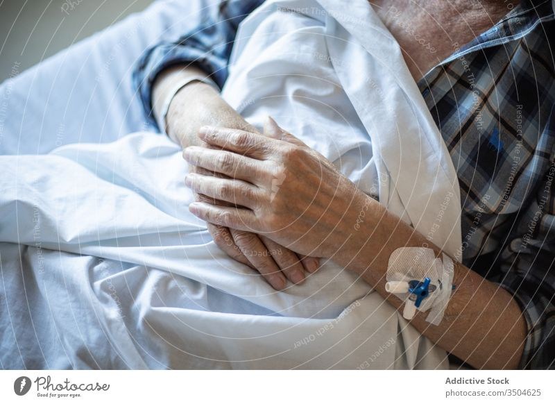 Senior male with catheter in hand sleeping in bed man patient intravenous hospital clinic medicine elderly illness therapy treat diagnosis cure equipment