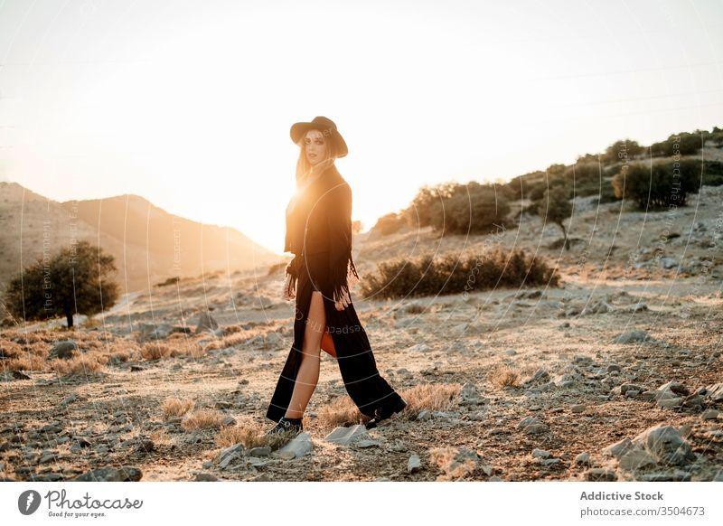 Stylish woman standing on rock in countryside style stone sunset hat walk outfit slime female model black trendy nature boulder sundown evening twilight dusk