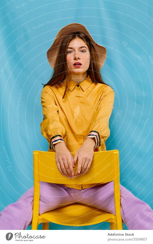 Stylish female model sitting on chair woman trendy style colorful outfit young fashion confident hat summer sensual urban millennial chill serious individuality