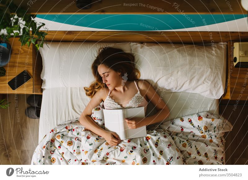 Woman asleep with book lying in bed woman read morning rest comfort relax cozy bedroom home lifestyle female blanket novel story wake up nap lazy early awake