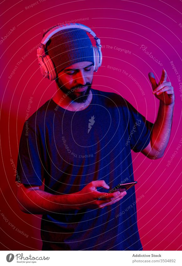 Modern man using smartphone and listening to music shaka sign modern style mobile phone red light male device gadget gesture headphones young beard sound