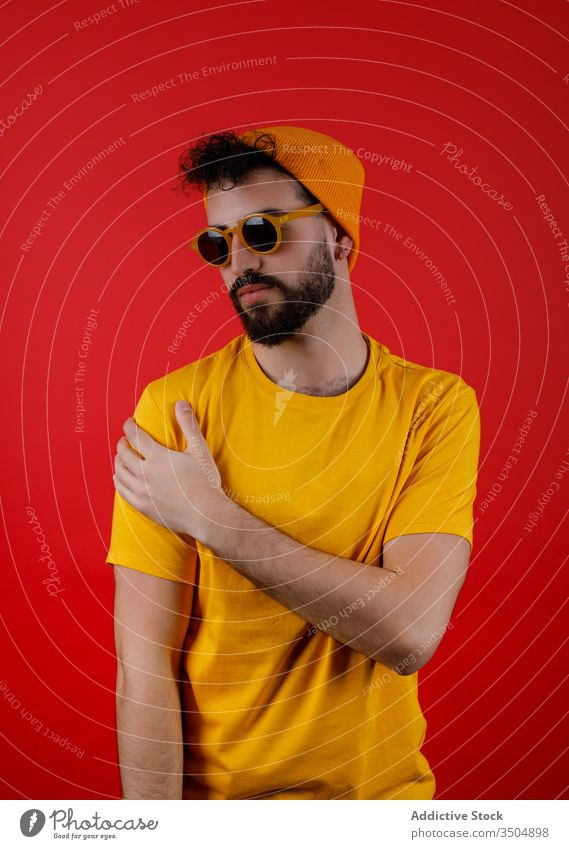 Confident bearded man in trendy outfit style modern urban confident touch shoulder young colorful bright male hipster serious casual yellow fashion cool vibrant