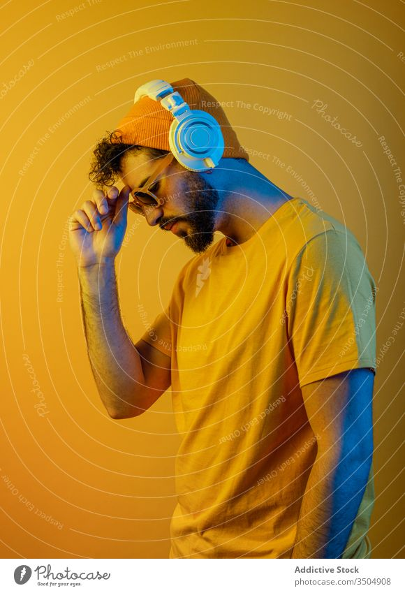 Bearded man with modern headphones urban style outfit music color bright male contemporary white yellow accessory hat sunglasses sound melody tune vivid vibrant
