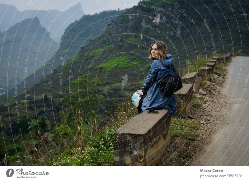 Young woman sitting on the edge of a mountain road, Attractive female bakpacker traveling by motorbike through northern vietnam. person nature lifestyle