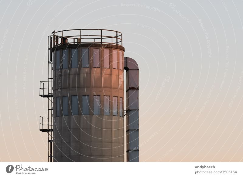 An old silo glows in the low beam afternoon architecture big building Business chemical construction container copy space cylinder depot distribution economy