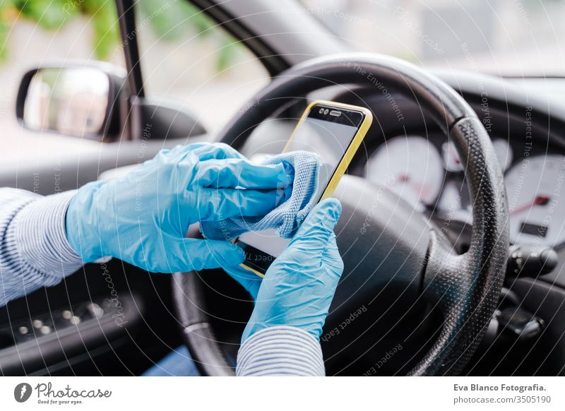 man disinfecting mobile phone with alcohol gel in a car wearing protective mask and gloves during pandemic coronacirus covid-19 driving protective gloves virus
