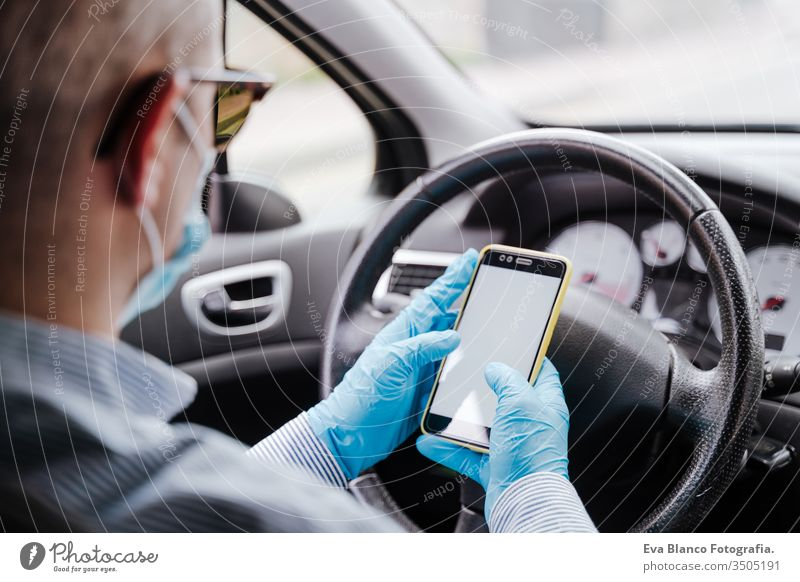 man using mobile phone in a car wearing protective mask and gloves during pandemic coronacirus covid-19 driving protective gloves virus coronavirus technology