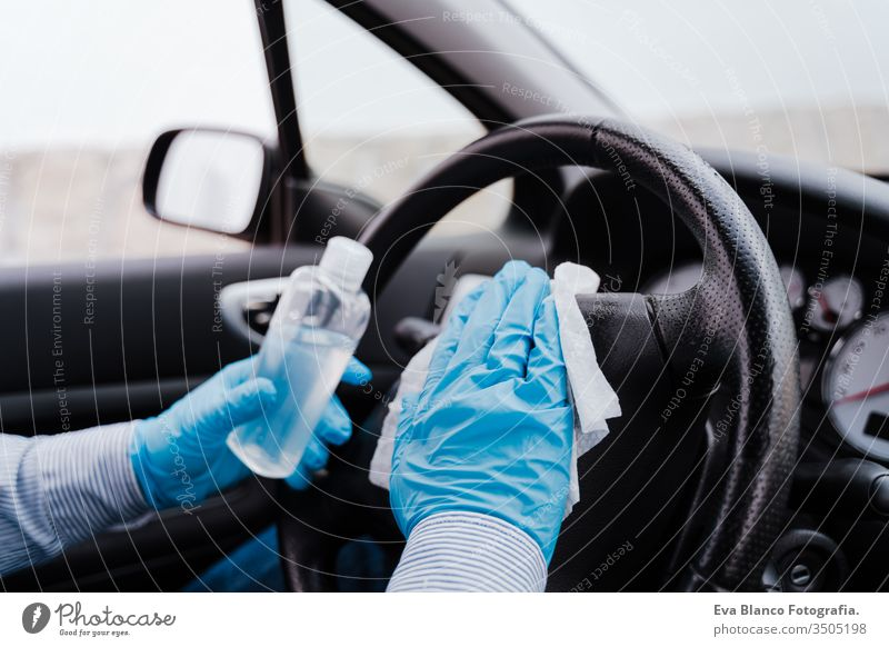 unrecognizable man in a car using alcohol gel to disinfect steering wheel during pandemic coronavirus covid-19 disinfecting get automobile transport wipe job