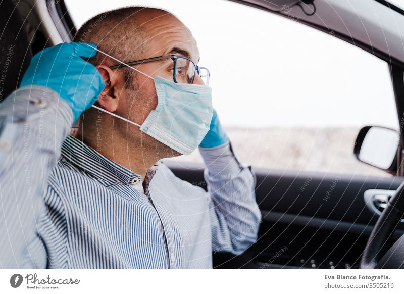 man in a car putting on protective mask and gloves during pandemic coronacirus covid-19 driving coronavirus protective gloves infect automobile health transport