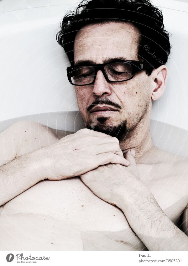 Completely relaxed, the man slept in his bathtub with his glasses on his nose, and his dreams were strangely contoured. Man Eyeglasses Sleep Facial hair Bathtub