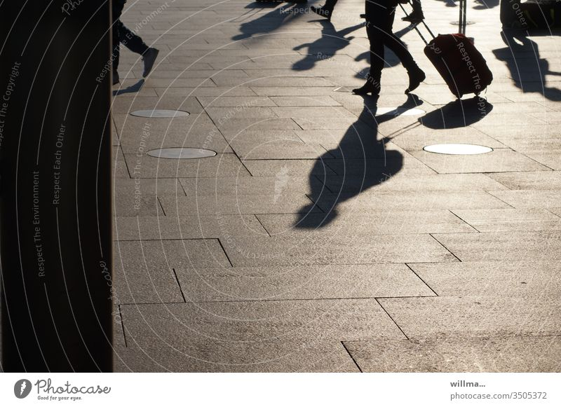Travellers with long shadows and wheeled suitcases on the station square Shadow people trolley Suitcase Train station Going sunny Group go away