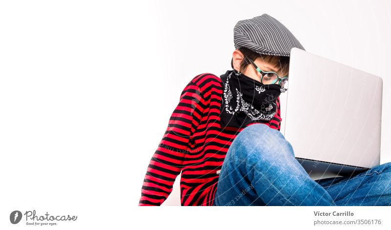 Cute boy with glasses on a white background with a mask using a laptop indoors adorable beautiful casual cheerful childhood color computer confident cool copy