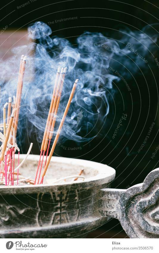 Smoking burning incense sticks in a bowl in front of a temple Joss sticks Smoke smoke Burn smoking smoke out Buddhism Hinduism Holy Asia Religion and faith