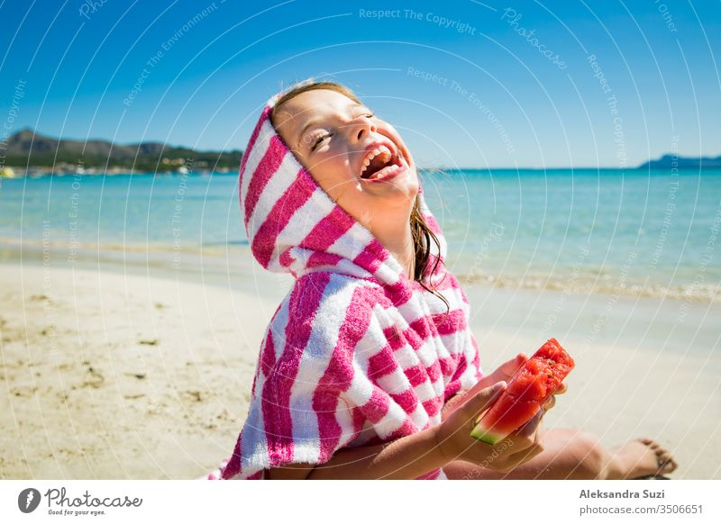 Cute happy little girl eating watermelon and laughing on the sand beach. Turquoise sea, blue sky, sunny summer day. Majorca, Spain activity beautiful candid