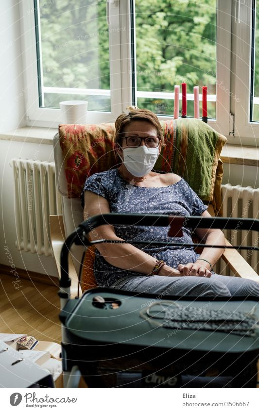 Woman in the risk group with mask and rollator sits alone at home in isolation due to the corona crisis Risk group covid-19 insulation Mask
