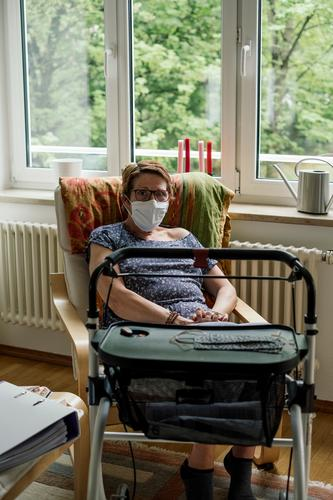 Woman in the risk group with mask and rollator sits alone at home in isolation due to the corona crisis Risk group covid-19 insulation Mask handicapped