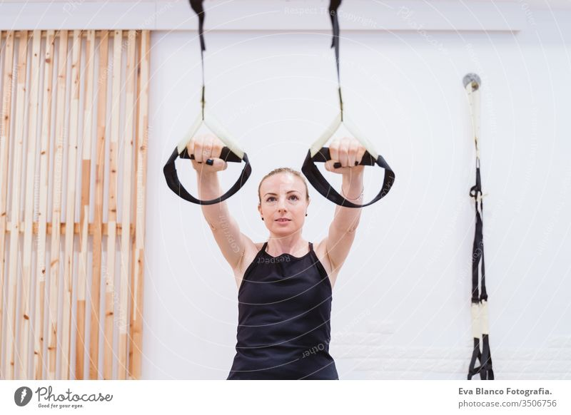 young woman practicing sport at the gym with trx. Healthy lifestyle dumbbells women friends healthy indoors fitness training heavy care push press-ups girl male