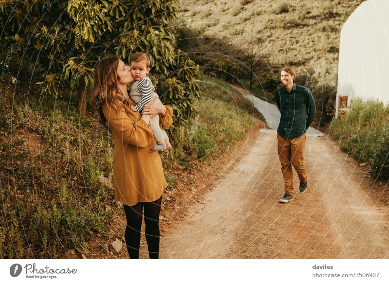 Woman kissing her baby son in nature, standing in a path, while man approaches to them with a smile. countryside loving family walk in nature tree happy parents