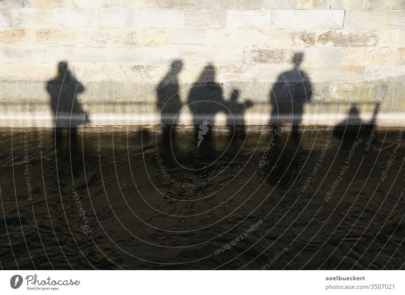 Shadows of a group of people sink into the water Group Water downfall Climate change River Wall (barrier) conceit Abstract differently Flood High tide Deluge