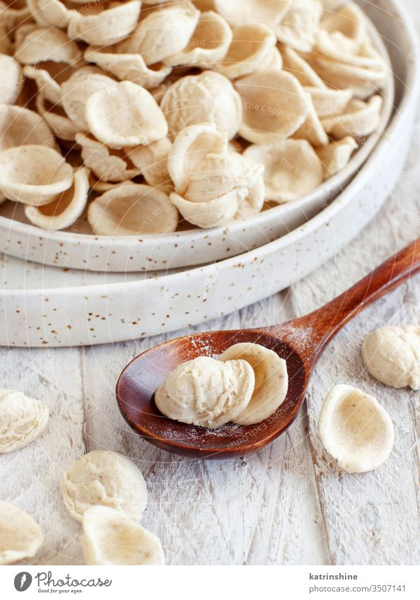 Fresh raw  italian pasta orecchiette apulia fresh dry traditional ingredient close up copy space spoon pastel cream plate diet flour handmade homemade