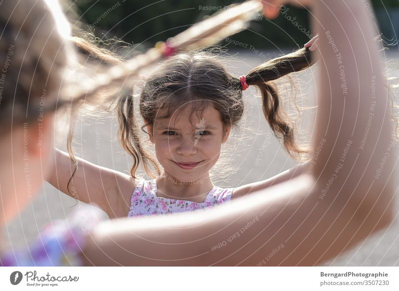 Two sisters play games Child gilr Summer Sun hair Smiley happy