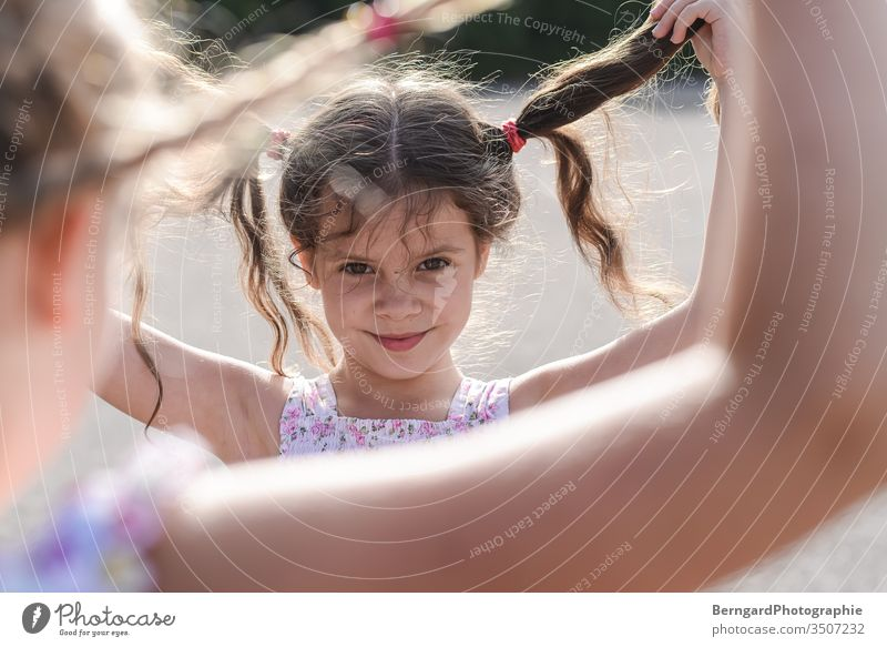 Two sisters play games Child girl playtime Smiley happy hair Sun Summer Portrait photograph eyes