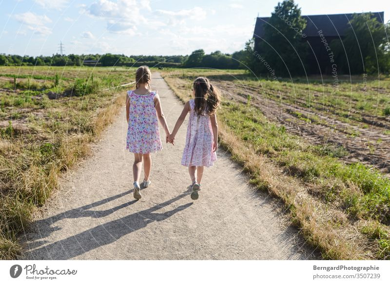 Two sisters play games off Field Village To go for a walk children gilrs Summer Sun nature