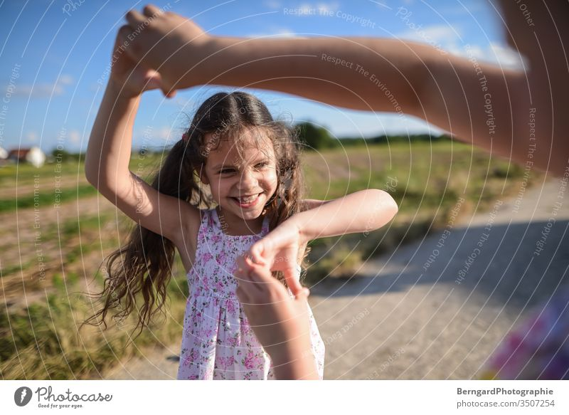 Two sisters play games Sister Girl Brothers and sisters Exterior shot Smiley happy buzzer playtime Sun Field light