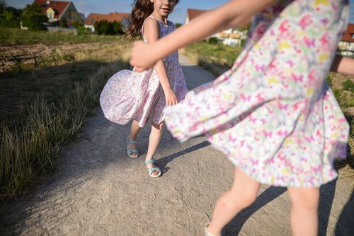 Two sisters play games Exterior shot Nature Day Sun Dress girl buzzer playtime