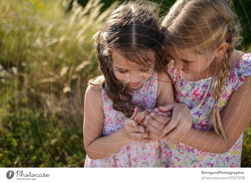 Two sisters play games Summer Light hair smile mystery playtime hands girls