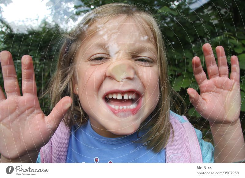 Child behind glass pane Infancy Playing Joy flat nose fun Funny Grimace grimace Face Nose Mouth Fingers Teeth Show your teeth Happiness Brash Window pane