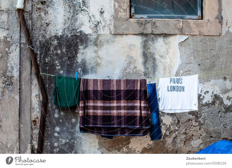 Longing - T-shirt with inscription Paris London hangs with other pieces of laundry on the line in front of an old wall in Sicily Wall (building) Clothesline