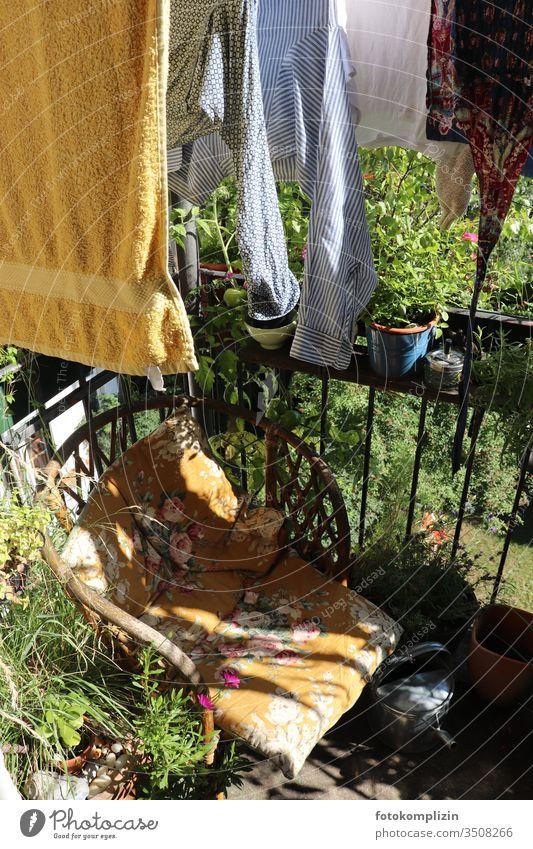 Wicker chair and clothesline between plants on balcony Cane chair Balcony Clothesline Living or residing Idyllic balcony flowery seat cushion Balcony life