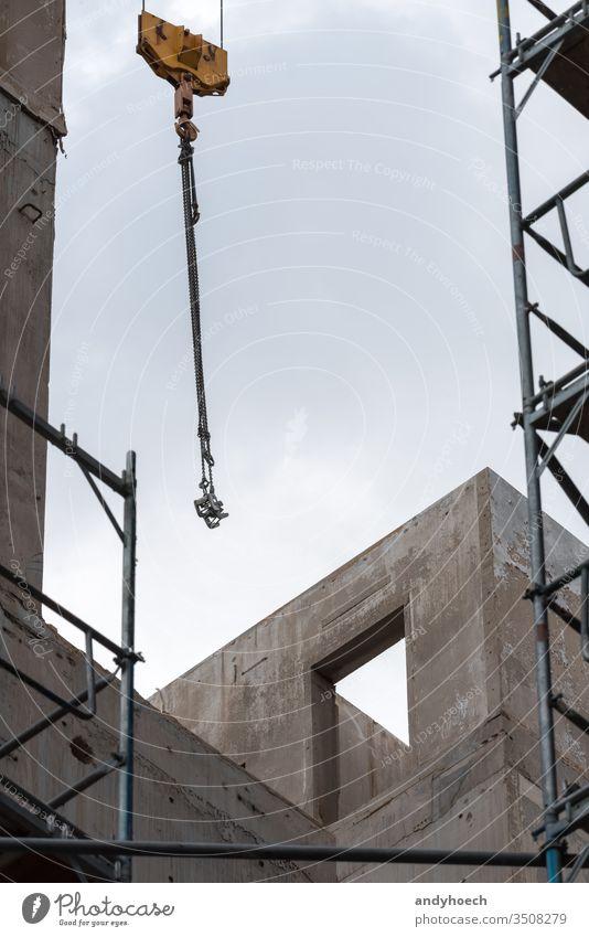 Crane hooks and scaffolding in front of an unfinished building apartment architecture built Business city concrete construction crane design development door