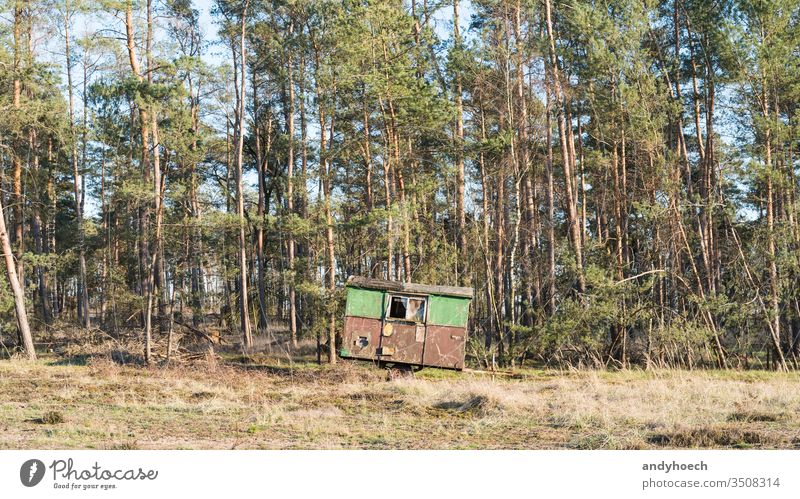 A construction trailer stands on the edge of a forest abandoned aged ancient Background beautiful broken camp camper campsite caravan coniferous damaged decay