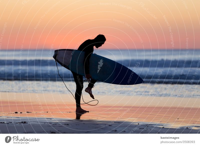 Silhouette of surfer on beach with surfboard. silhouette sunset summer sport man surfing ocean water nature sunrise active fun sand recreation lifestyle travel
