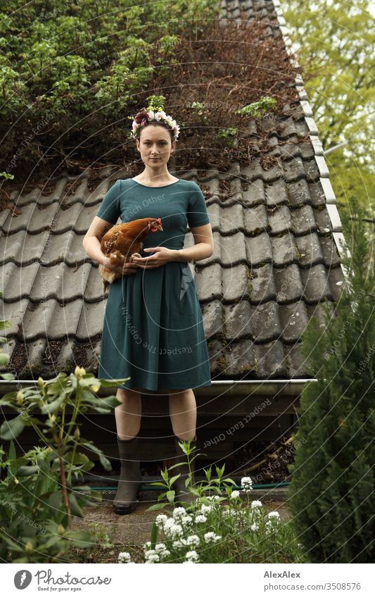 Young woman with a wreath of flowers in her hair stands in front of the summer house and holds a brown chicken in her arms Central perspective