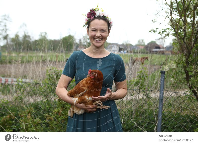 Young woman with wreath of flowers in her hair is standing in the garden holding a brown chicken in her arms Central perspective Shallow depth of field Day