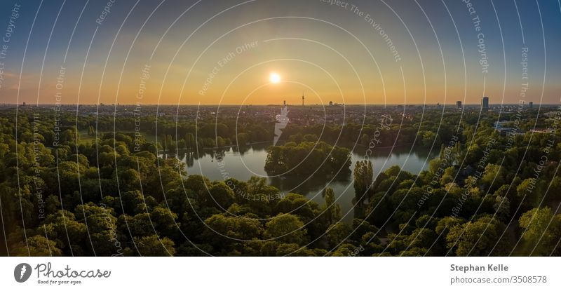 An idyllic park in the Englischer Garten of Munich with a beautiful lake as an aerial. munich nature beatyful sunset drone sky trees green summer boat skyline