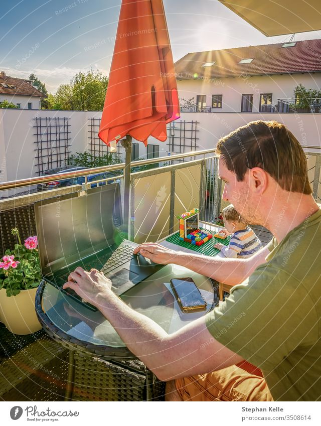 The Ministry of the Interior, father and son work together with their laptops at home on the balcony while the sun is shining. New lifestyle due to corona, Covid 19 pandemic.