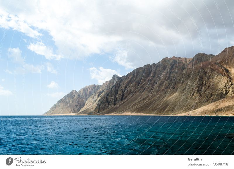 blue sea and high rocky mountains against the sky and clouds in Egypt Dahab South Sinai Middle East Near East Red Sea background day horizon landscape