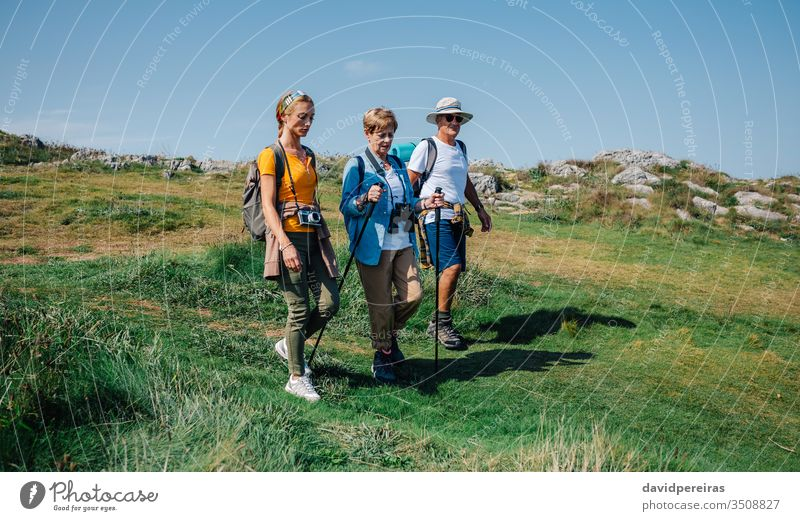 Family practicing trekking together outdoors family hiking mountain field walking nature senior journey tourism people hikers backpack women girl daughter