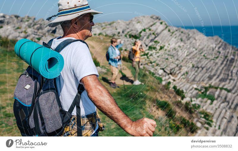 Senior man trekking looking at the landscape hike senior mountain mat backpack nature hat sunglasses countryside backwards summer hikers retired pad sea ocean