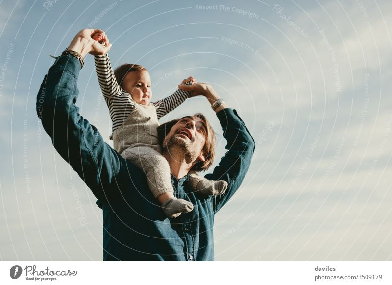 Handsome man giving a piggyback ride to his baby son outdoors. together stroll spring smiling parenting little happiness childhood face care adorable portrait