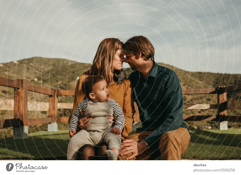 Lovely couple caring to their baby son with mountains in the background. parenthood boy holding romantic hugging dad mom lookout care trip leisure relationship