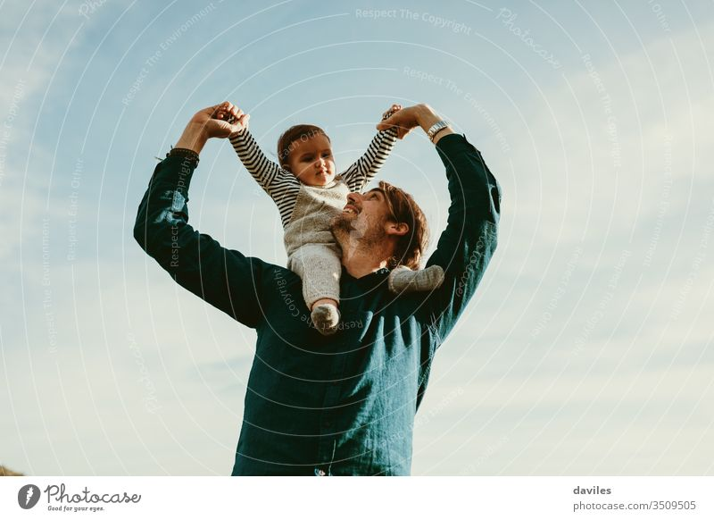 Handsome man giving a piggyback ride to his baby son outdoors. young fatherhood arms handsome male person sky background cute white looking lovely 30s 1 year