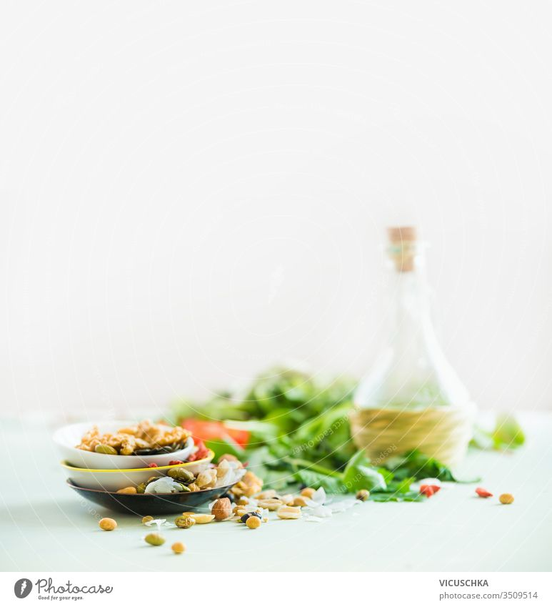 Healthy salad making ingredients on white table at light sunny wall background. Fresh kitchen herbs. Nuts topping. Olives oil. Salad dressing . Diet or vegetarian food concept.
