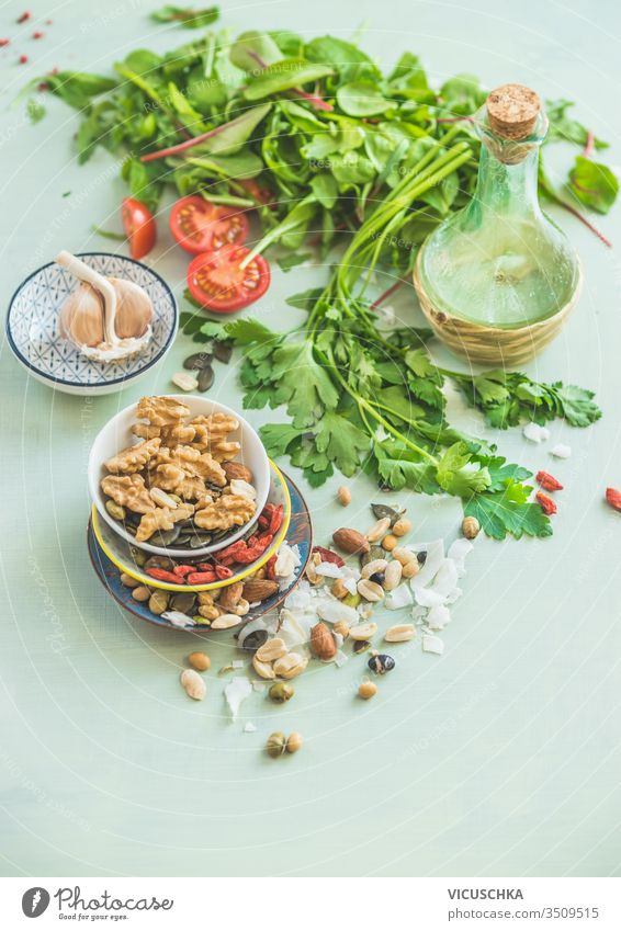 Healthy salad making ingredients. Fresh kitchen herbs. Nuts topping. Olives oil. Salad dressing . Diet or vegetarian food concept. healthy fresh nuts olives oil
